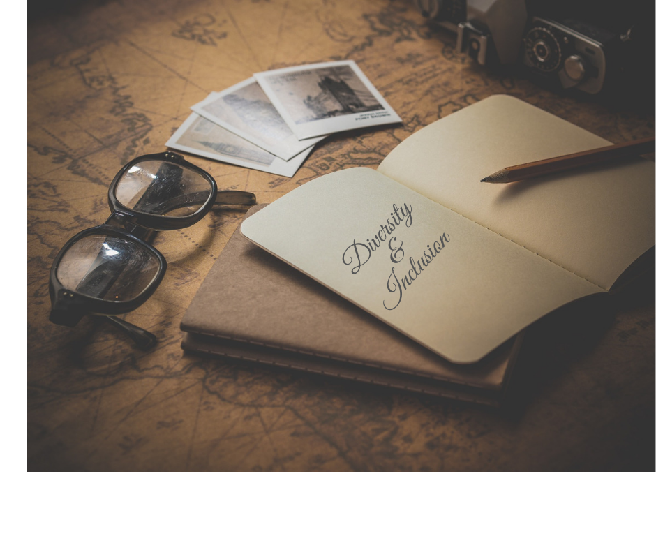 """A desk with the world map engraved into it. On top of the desk sits a notepad with the words """"diversity and inclusion"""" as well as glasses, old polaroid images, and a polaroid camera. The image is meant to set the scene for writing about your travels, culture, and diversity and inclusion."""