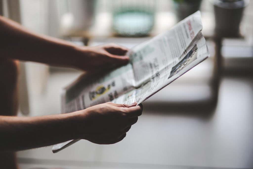 Image is focussed on hands holding a newspaper with a blurred background. Image is meant to represent news media in