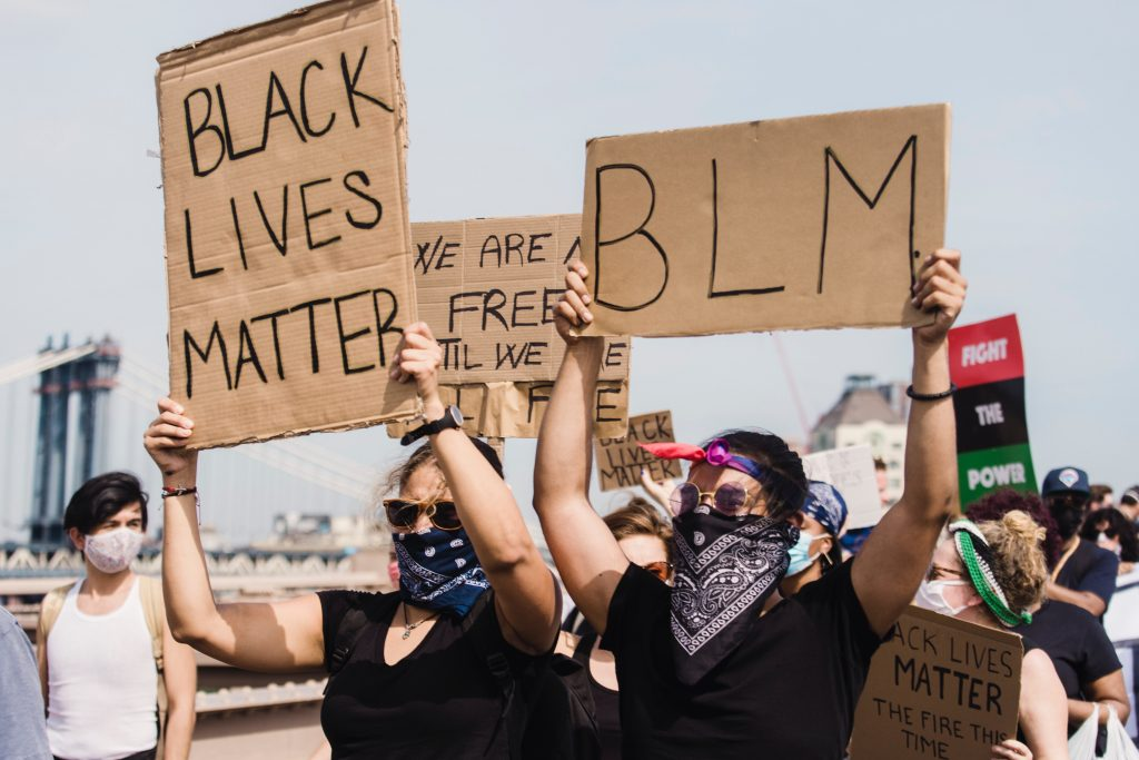 A crowd of Black Lives Matter protestors fighting racism on a bridge in America.
